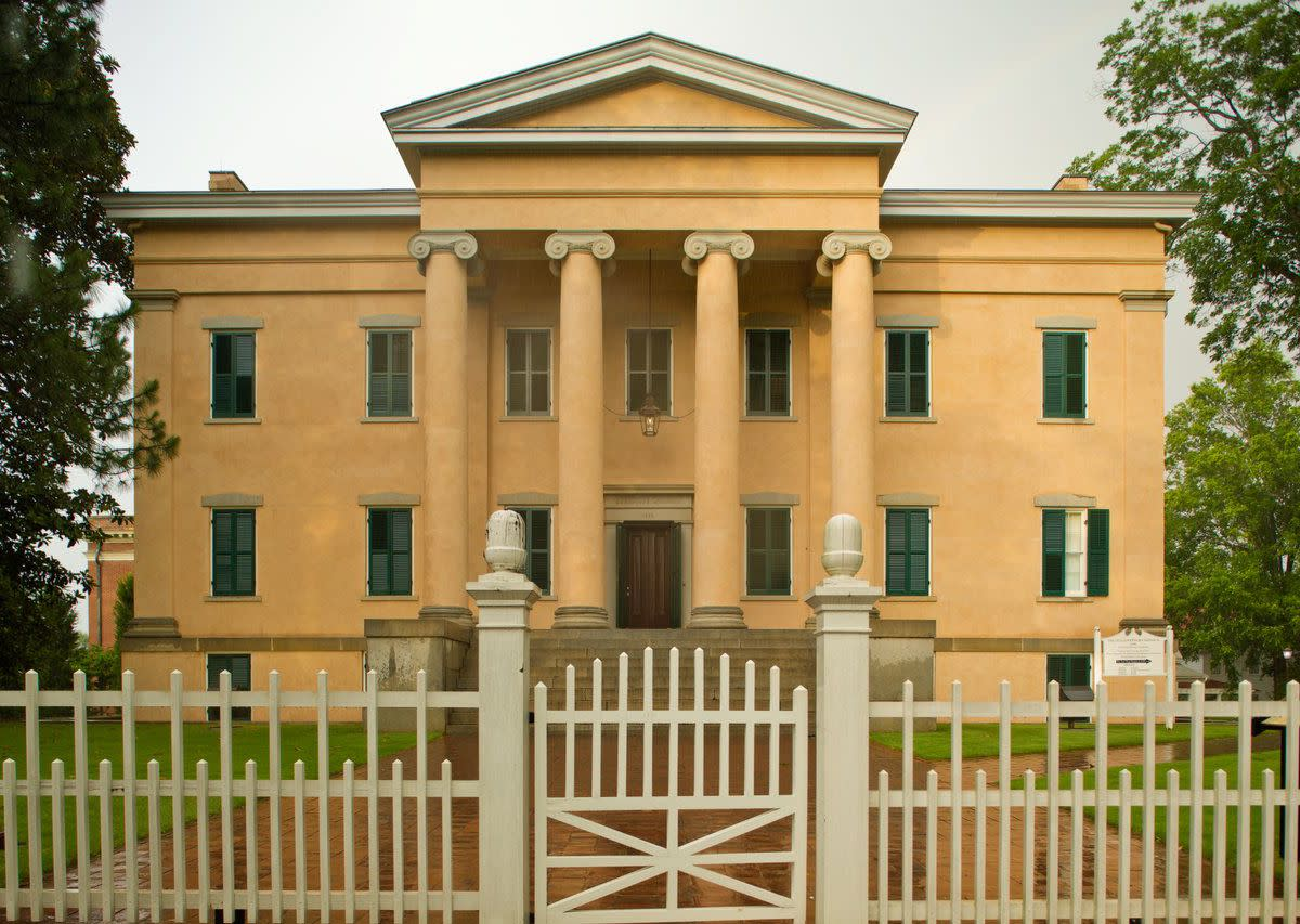 The exterior of Old Governors Mansion in Atlanta. The facade is yellow with columns in front. There is a fence and a lawn with trees in front of the house.