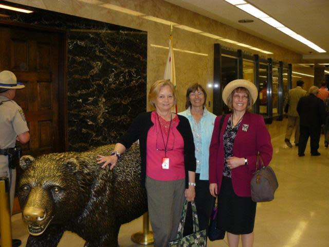 Carol, Janet and Cindy pose with the bear in front of the Governor's Office