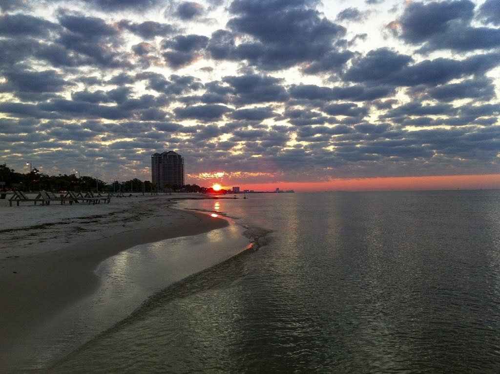 Sunrise over the ocean, with poofy gray clouds, a beach to the left, and a highrise in the distance, in Coastal Mississippi.