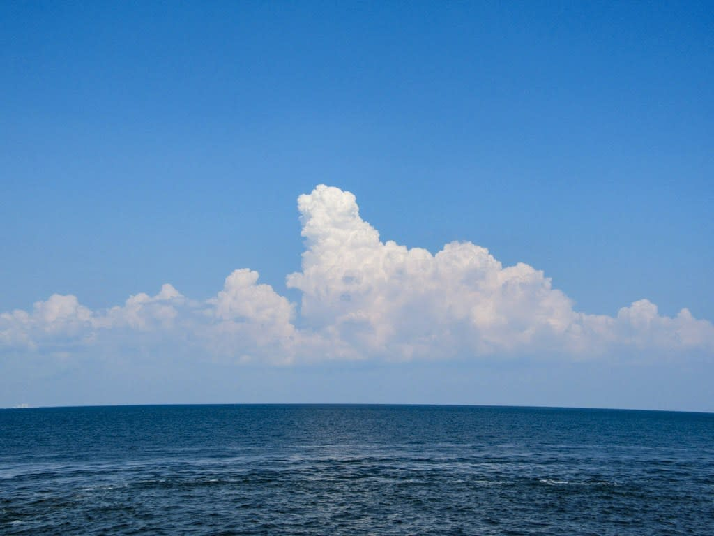 A broad expanse of deep blue water under a blue sky with puffy clouds.