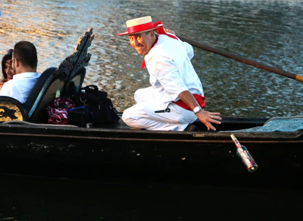 A gondolier drops a message in a bottle during a Gondola Adventures ride in Irving, TX