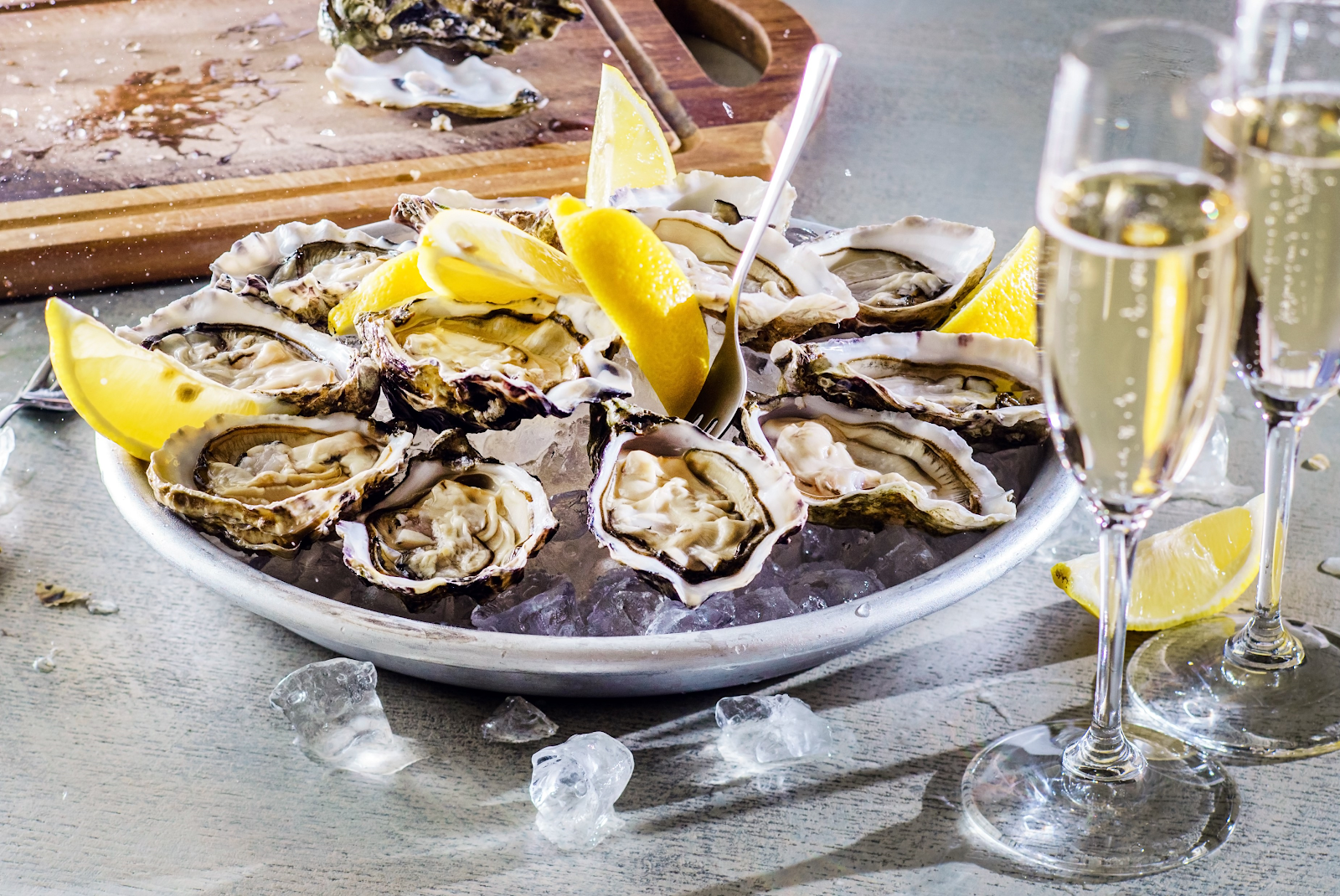 A platter of fresh oysters on the half shell is served on ice with lemon wedges.