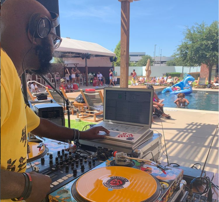 A DJ entertains poolside guests with music at The NYLO Las Colinas Hotel pool.