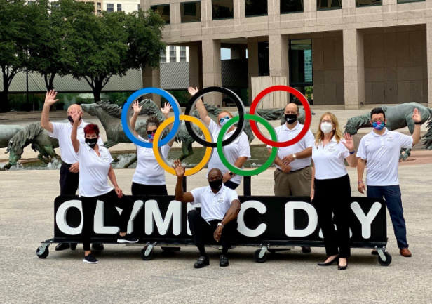 People In Masks Standing Around And Waving By An Olympic Day Sign