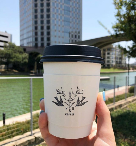 A customer shows off their fresh cup of Pax & Beneficia coffee in Irving.