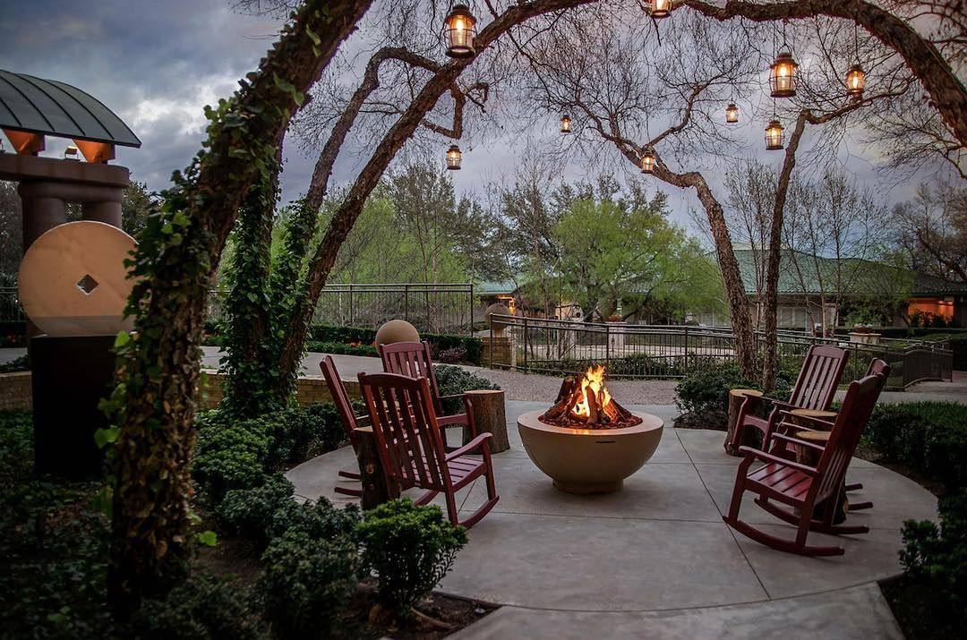 Rocking chairs wait around a fire pit at the Four Seasons Resort at Las Colinas while lanterns hang overhead.