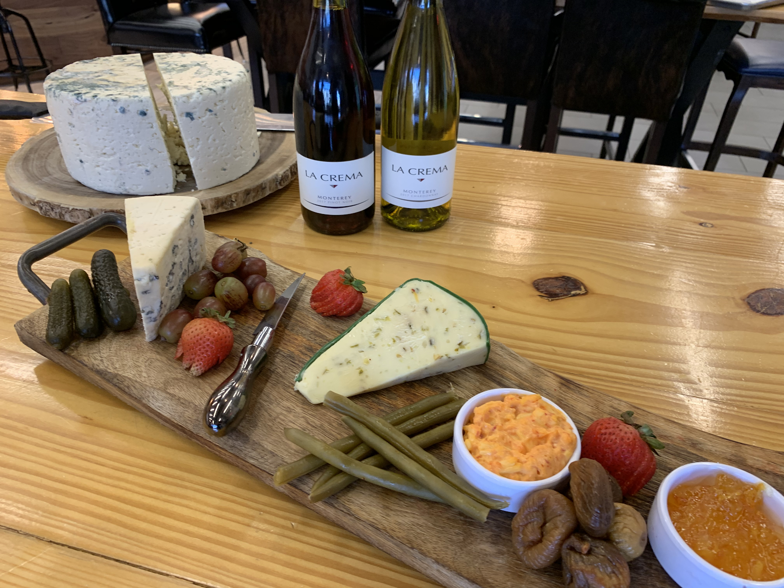 A cheese board and bottles of wine at Nosh and Bottle in Irving, TX