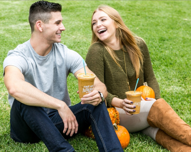 Couple On Grass Sharing A Smoothie From Nekter Juice Bar