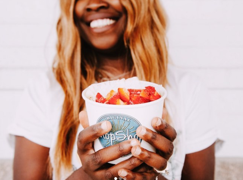 A woman holds up her strawberry-topped treat from Irving's Original Chop Shop.