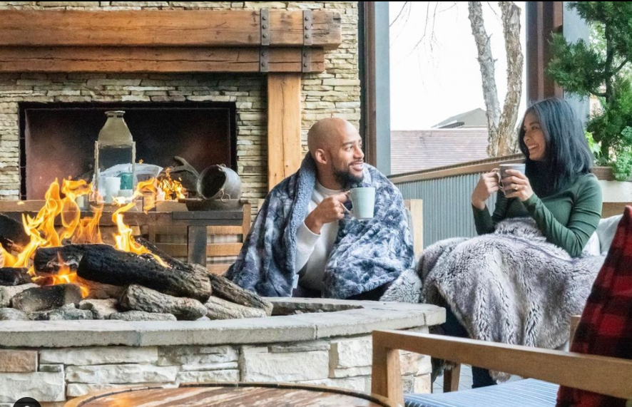 Couple snuggled under blankets sitting by the outside fire at the Four Seasons Resort at Las Colinas