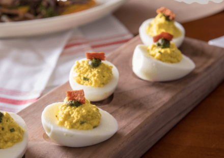 Deviled eggs from Whiskey Cake in Irving, TX are served up on an elegant wooden tray.
