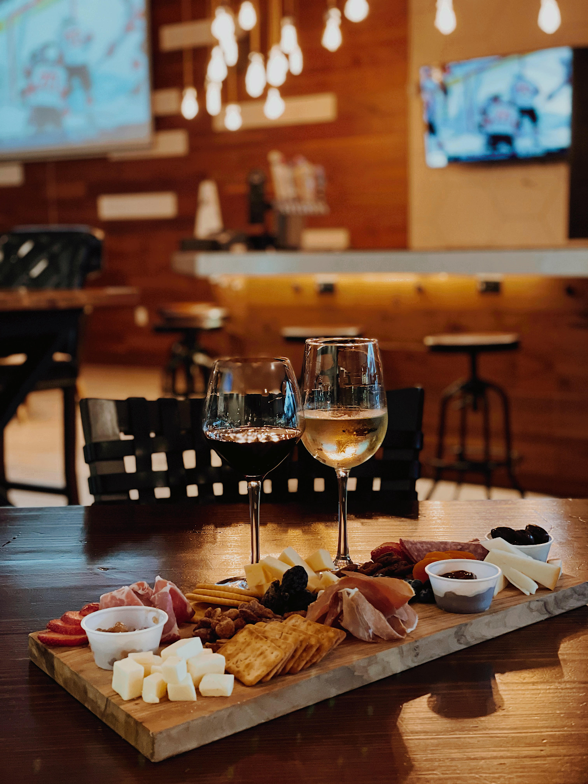 Charcuterie board with glasses at wine at Nosh & Bottle in Irving, TX