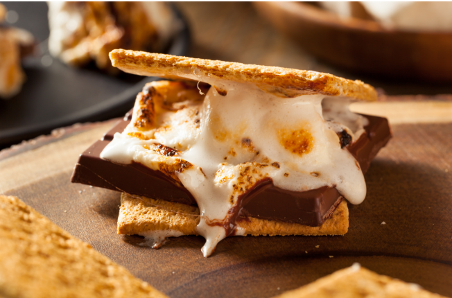 Gooey toasted marshmallow sits on chocolate, nestled between two graham crackers, making the picture-perfect s'more.