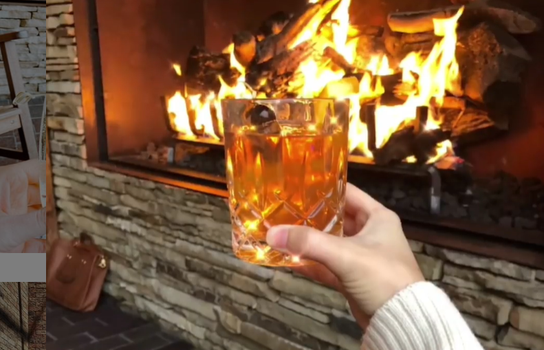 A guest at the Four Seasons Resort at Las Colinas enjoys a nice drink in front of a roaring fire.