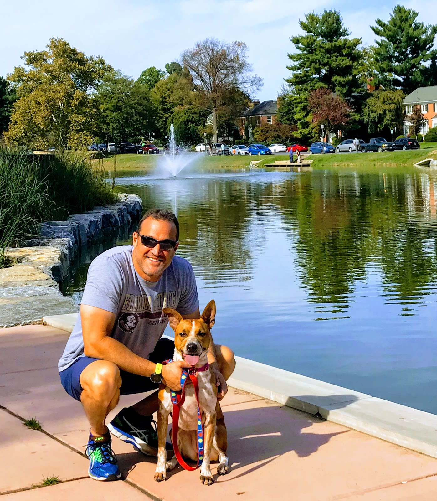 Man and dog posing in front of water in Frederick, MD