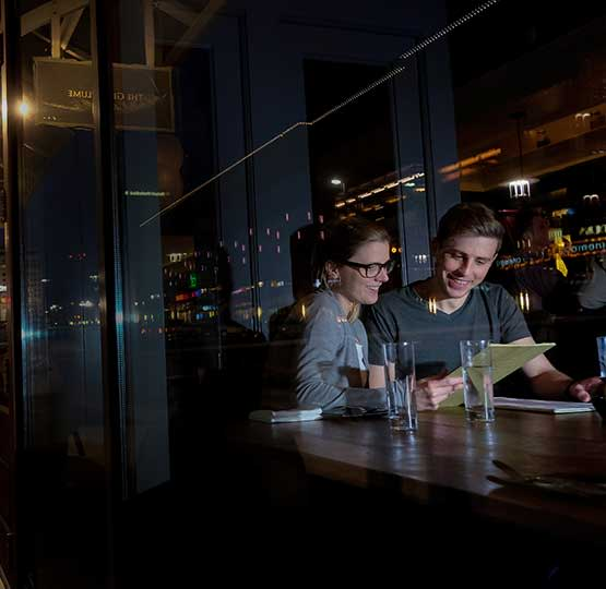 Seen through the front window with a street reflection, a couple looks at a menu inside The Grey Plume in Omaha, Nebraska