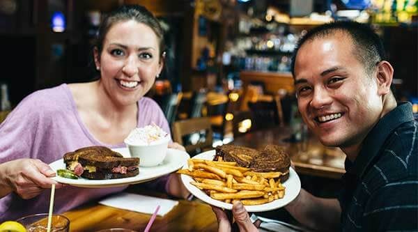 A man and a woman hold up plates of Reuben sandwiches, coleslaw and French fries at The Crescent Moon in the Blackstone District of Omaha, Nebraska