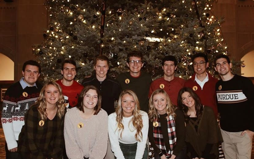 A group of Purdue students pose in front of the 2018 Purdue Memorial Union decorated tree.