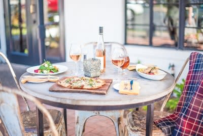 Image may contain Furniture Dining Table Table Food Pizza Human Dating Person Glass Chair Meal and Linen
