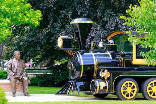 Photo of Purdue's Boilermaker Special, a black and gold locomotive, driving by a statue of John Purdue on Memorial Mall