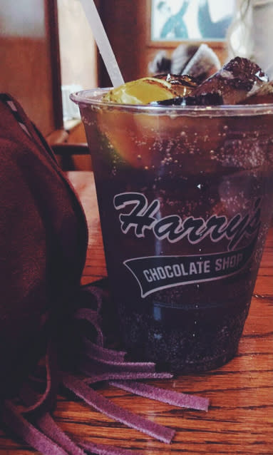 Photo of rum and Coke drink and a purple suede purse with fringe sitting on the bar at Harry's