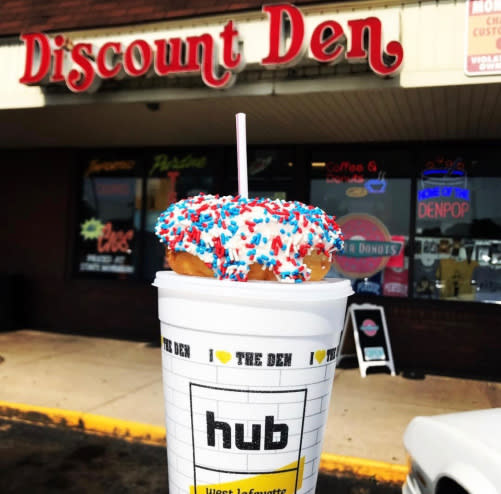 Photo of a red, white and blue donut atop a Den Pop in front of the Discount Den store