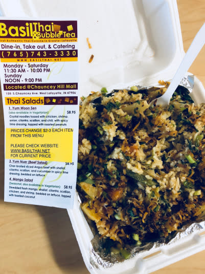 Photo of Basil Thai's curry pineapple fried rice in a to-go box next to a menu