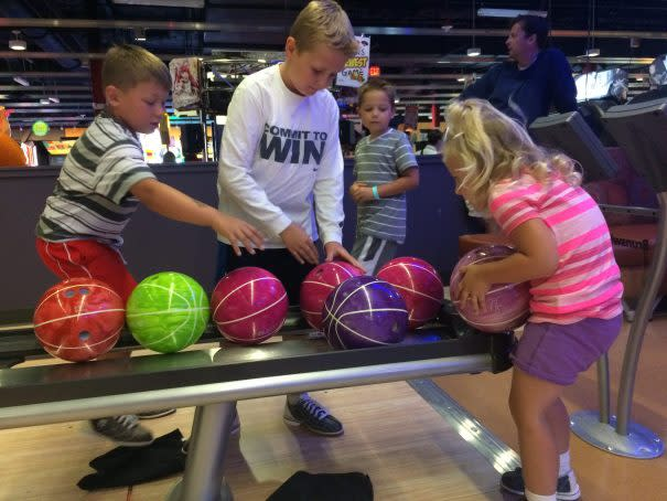 group of kids choosing their bowling ball at the bowling alley