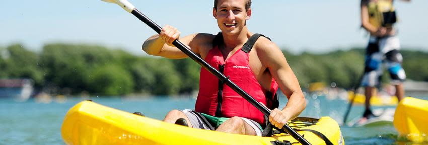 A man kayaks on Canandaigua Lake during a hot summer day