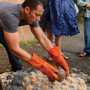 Diego Valles removes his students' ceramics from a wood-fired kiln he made out of a steel bucket.