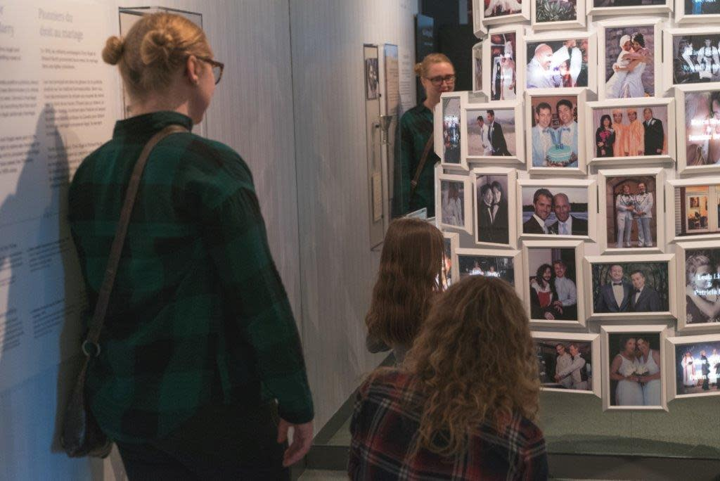 A child points at a picture in a tower of pictures while two adults look on.