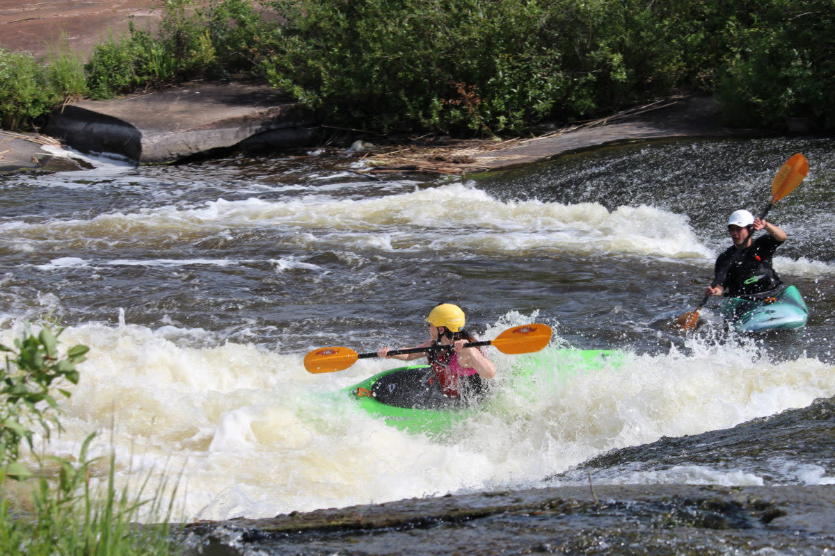 Tamara paddling through tumultuous water at the end of the rapids.