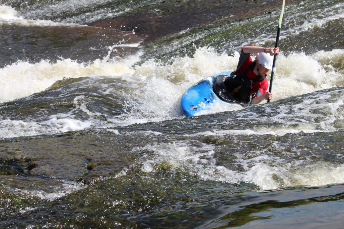 Prairie Whitewater owner/lead instructor Steven Walker turns his kayak into the rapids.