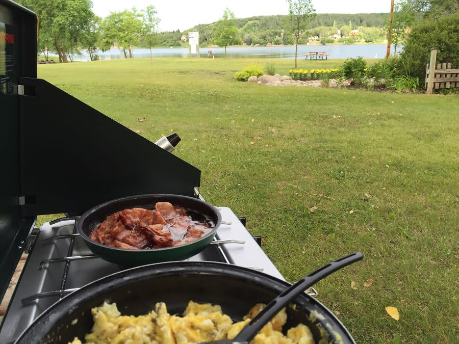 Cooking bacon and eggs on a campstove next to Minnedosa Lake