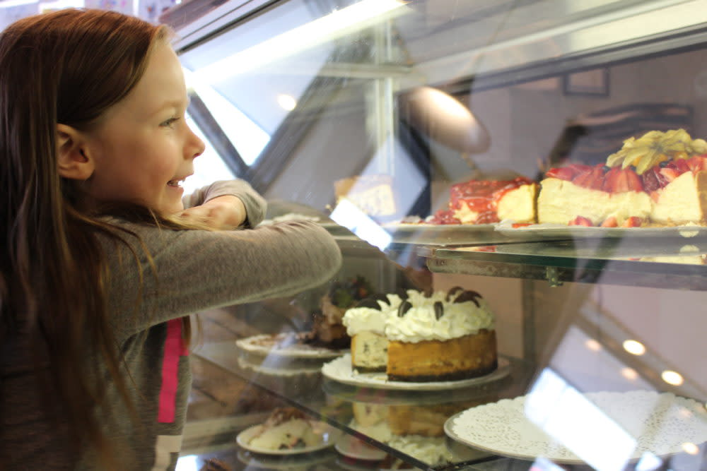 Child leaning on display case window looking at cheesecakes