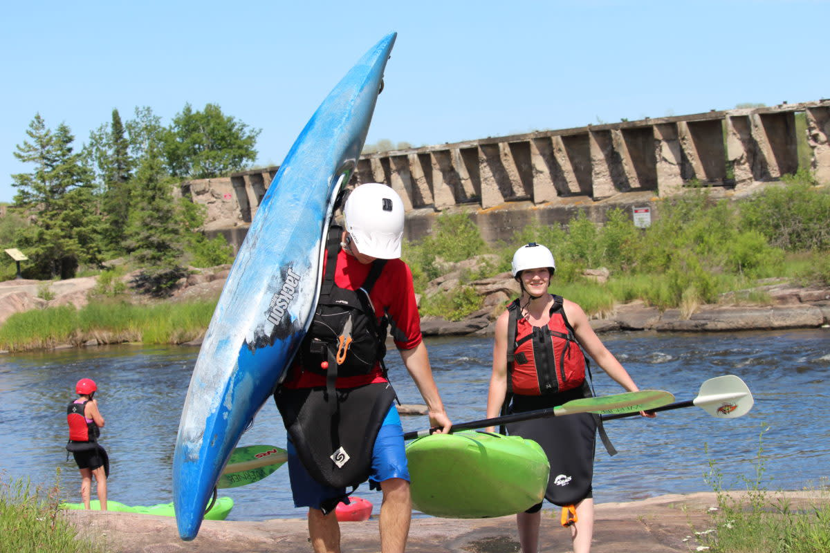 Carrying two kayaks along the shore by the water.