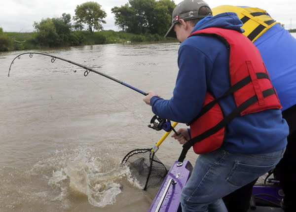 Oliver Sachgau reels in a channel catfish on the Red River.