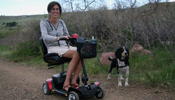 A woman uses a scooter on a Boulder trail with her service dog