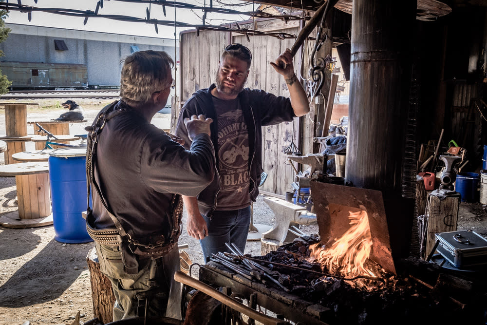 Blacksmith Will Frary passes down the craft to an apprentice at The Grapevine Blacksmith Shop.
