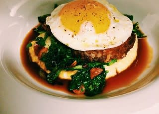 Cotechino sausage with polenta, broccoli rabe, and roasted chicken sugo with a sunny side up egg