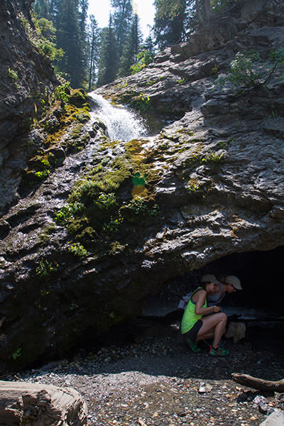 Hikers descend into the grotto under Donut Falls