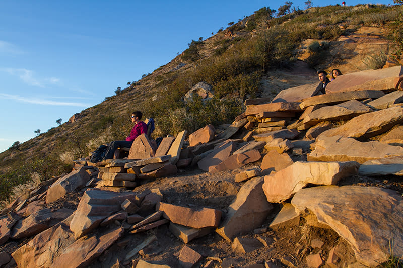 Hikers relax on stone furniture
