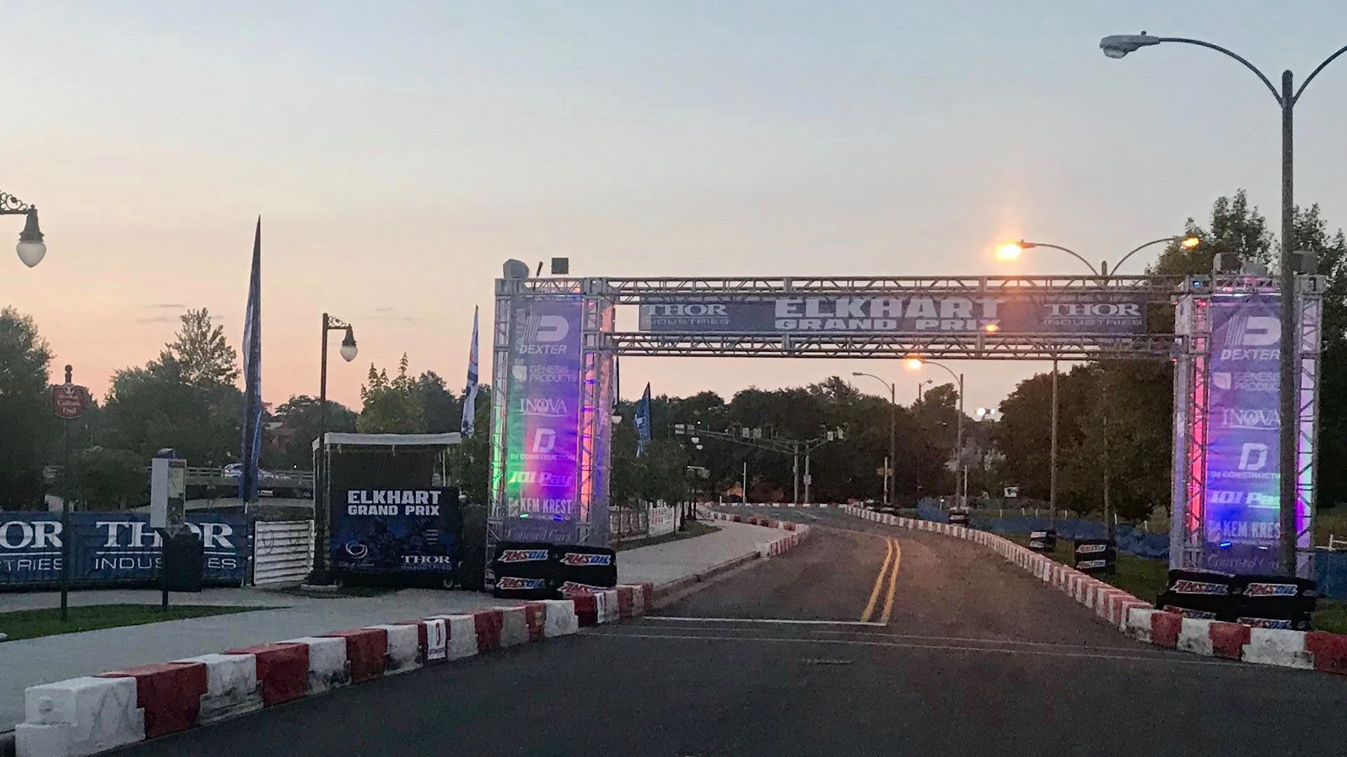 """Streets set up with red and white barriers with a banner above that says """"Elkhart Grand Prix"""""""