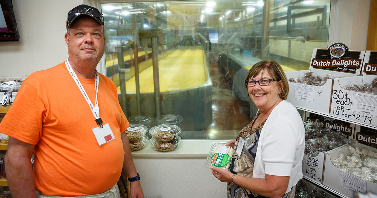 A man and woman standing in front of a window that looks into a cheese production factory. The woman is holding a container of cheese