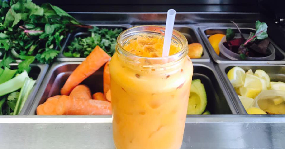Orange-colored juice in a glass jar in front of a service counter filled with fruits and vegetables
