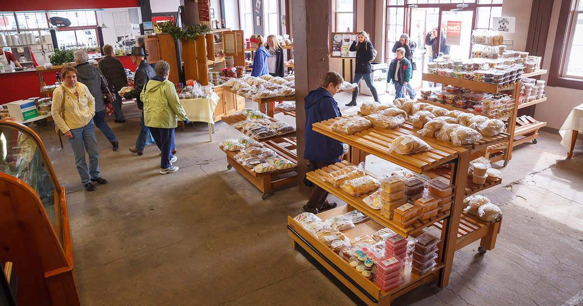 Wide shot of a bakery with people in coats browsing displays of bread and cookies