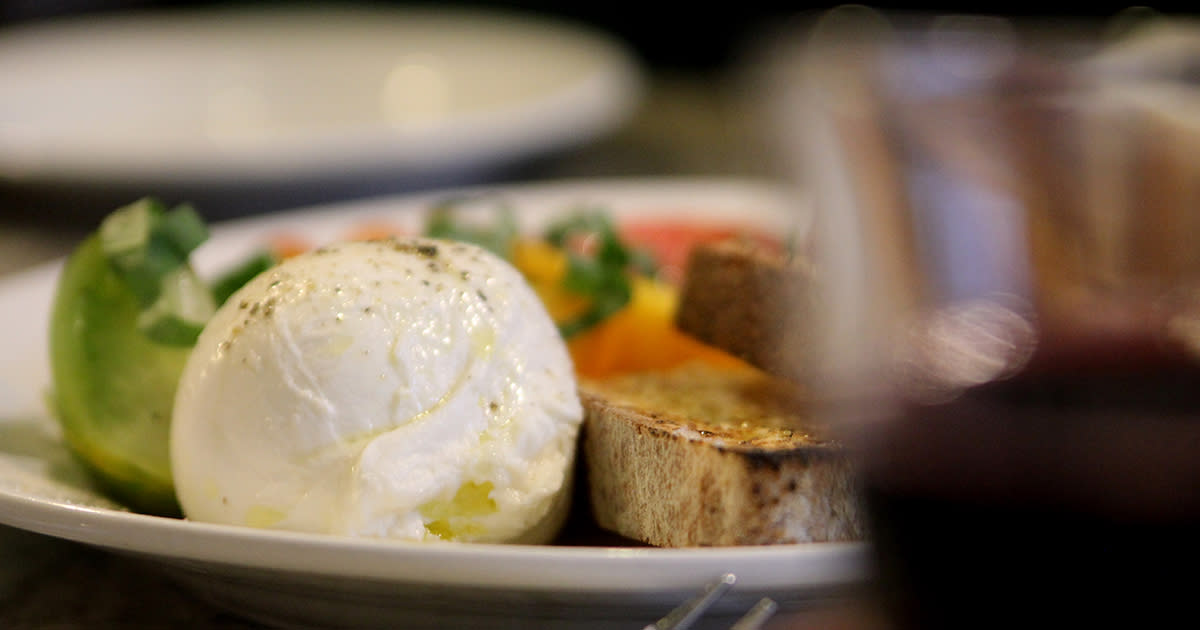 Close-up of a plate food that includes a fresh mozzarella ball in the forefront