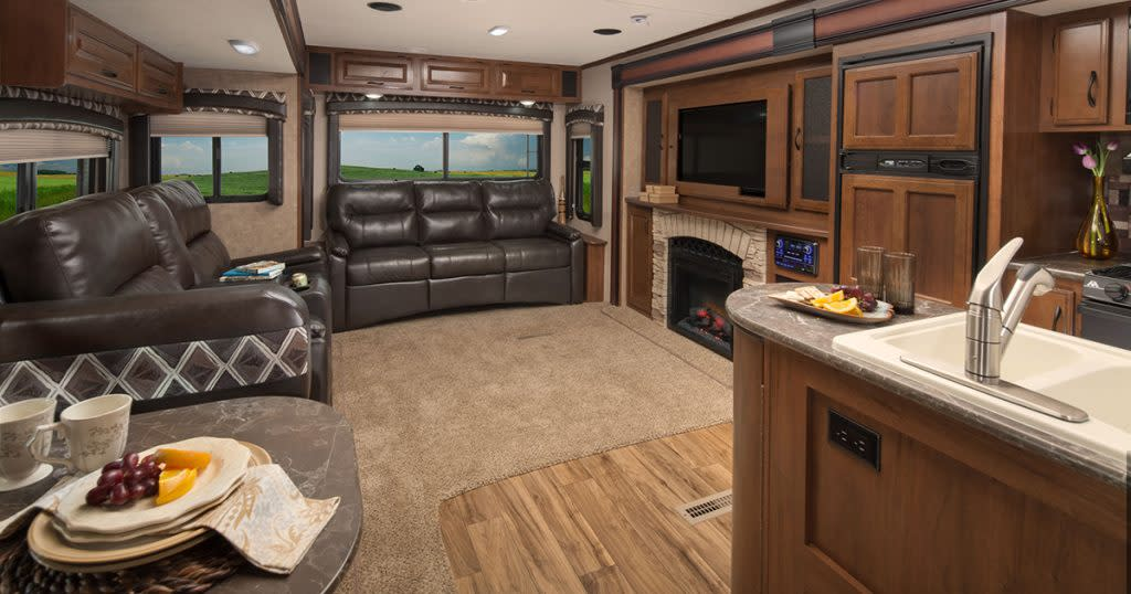 Fully- furnished RV interior with leather couches, kitchen area, and a fireplace