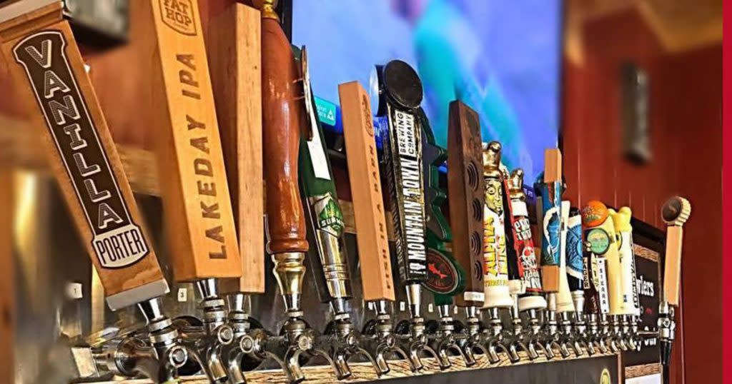 Close-up of a row of unique bar taps in front of an out-of-focus flat screen TV