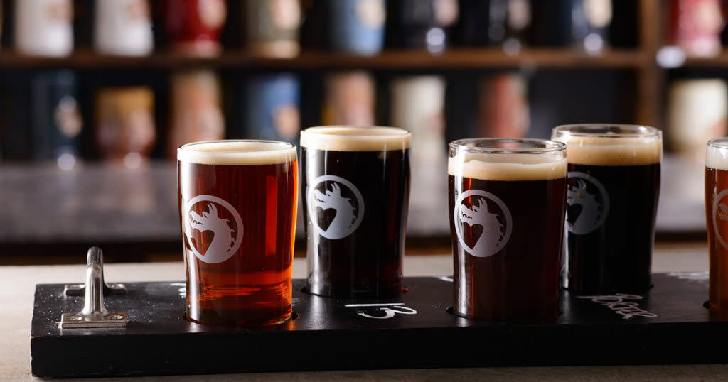Five beers in glasses with a dragon logo sit on a wooden board on a bar top with out-of-focus taps in the background